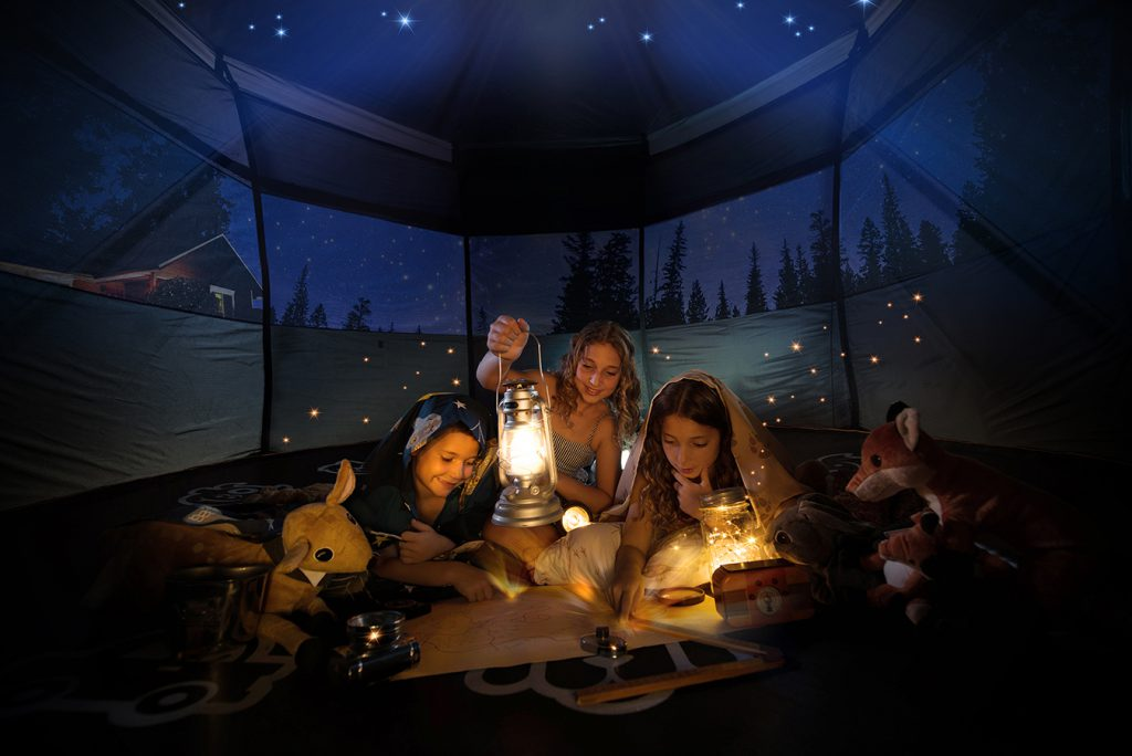 Vuly image of children in tent looking at a treasure map by lamp light, at dusk with magical fireflys